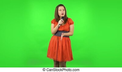 Cute girl is singing into a microphone and moving to the beat of music. Green screen