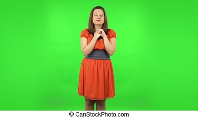 Cute girl is waiting in anticipation with pleasure. Green screen