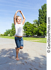 Cute girl with blond hair jumping on one leg