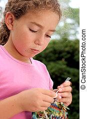 Cute girl knitting. Motion blur on hand.