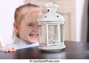 Cute girl laughing before luminaire with candle