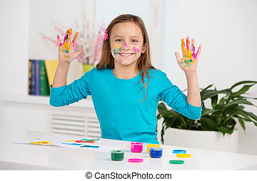 cute girl lifting hands stained with paint. waist up schoolgirl smiling and sitting at table
