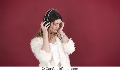 Cute girl listens to music with headphones