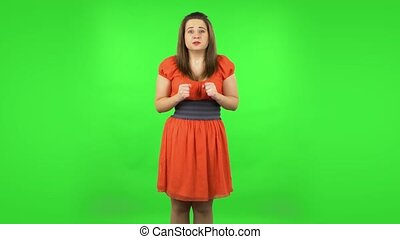 Cute girl looking at camera with anticipation, then very upset. Green screen