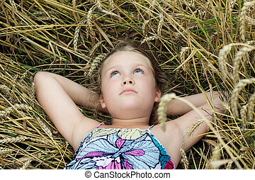 cute girl lying in a field and dreaming