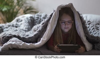 Cute girl lying under blanket with touch pad - Cute girl...