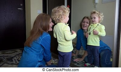 Cute girl measure necklace with her mother in front of mirror