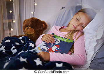 Cute girl napping with book