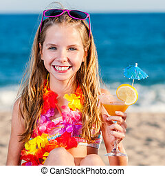 Cute girl on beach holding fruit cocktail.