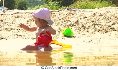 Cute girl on beach playing with watering pot