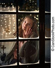 Cute girl outside the window at his home in anticipation of New Year miracle.