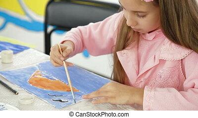 Cute girl painting at kindergarten