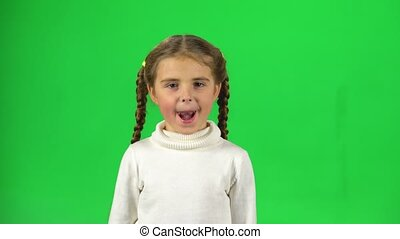 Cute girl playing and make funny face, show tongue out on green screen