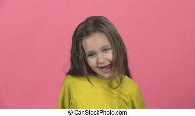 Cute girl playing and make funny face, show tongue out on pink background. Slow motion