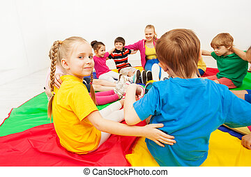 Cute girl playing circle games with friends in gym