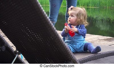 Cute girl playing on pier - Funny little girl playing with...
