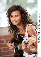 Cute girl playing the guitar. - Close up portrait of cute ...