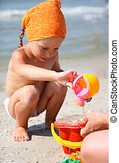Cute girl playing with beach toys on tropical beach