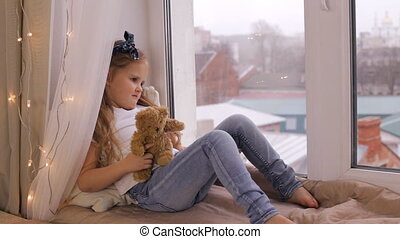 Cute girl playing with her teddy bear and sitting on window sill