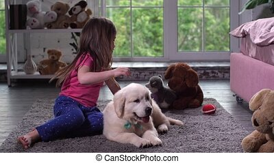 Cute girl playing with puppy sitting on floor - Playful...