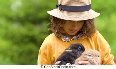 Cute girl holding real rabbit. Kids play with pets in summer day. Adorable little easter bunny.