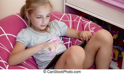 girl playing with tablet - cute girl playing with tablet at...