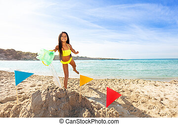 Cute girl playing with water and sand on the beach