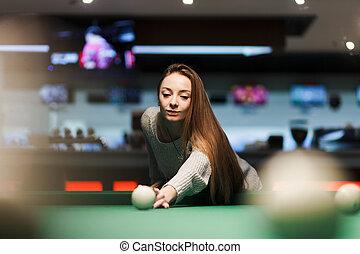Cute girl plays billiards in a bar