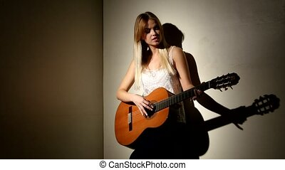 Cute girl plays on the acoustic guitar with bright emotions -  isolated on black background.