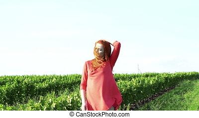 Cute girl posing in the green wheat field. Slowly