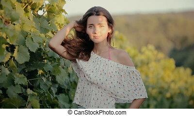 Cute girl posing near the vine in summer