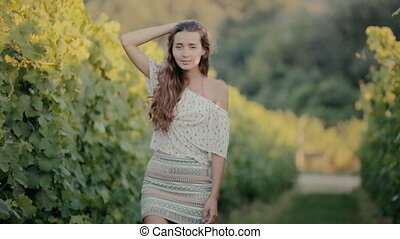Cute girl posing near the vine in the summer