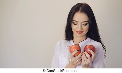 Cute girl posing with two juicy apples and smiling to camera 4K