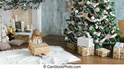 Cute girl, preschool child, opening presents on Christmas day. Little girl opening a gift on Christmas morning