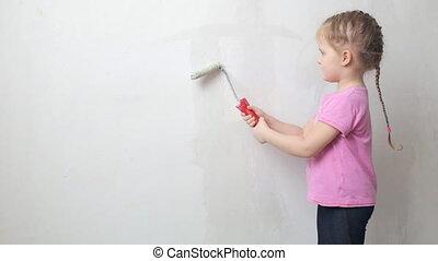 Cute girl priming a wall