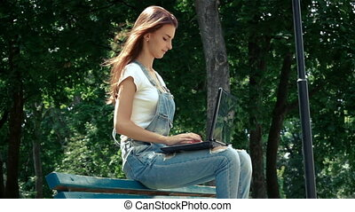 cute girl prints on a laptop while sitting on the street in summer
