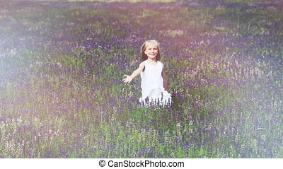 Cute girl ranning across the field. Child is in a white dress