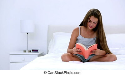 Cute girl reading a book on bed at home in bedroom