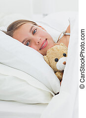 Cute girl relaxing with her teddy bear