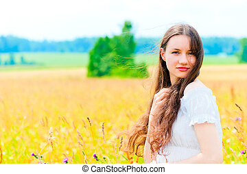 cute girl resting in a field with flowers