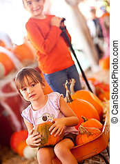 Cute Girl Riding Wagon with Her Pumpkin and Sister