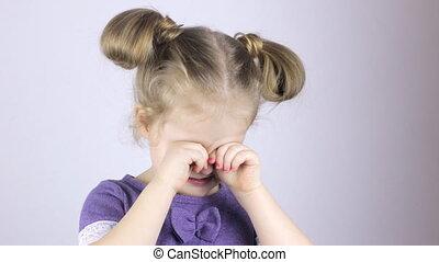 Cute girl rubbing her eyes
