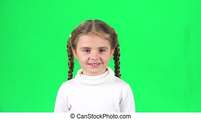 Cute girl screaming with smile on green screen in studio. Slow motion