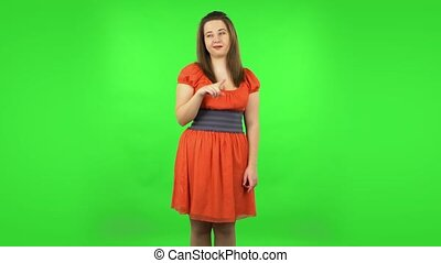 Cute girl smiling and showing heart with fingers then blowing kiss. Chubby girl in a coral dress with straight hair medium length and light eyes on green screen at studio