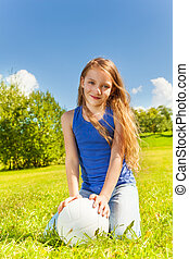 Cute girl sit in grass with ball