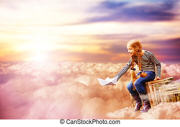 Imagination concept girl sitting near the pond holding white paper boat dream like image in the clouds