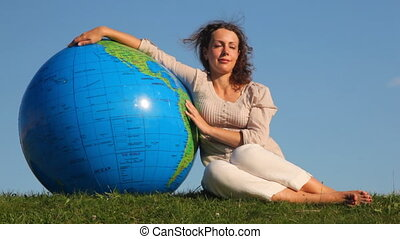 cute girl sits relaxing in grass and rests on large inflatable ball at form of Earth against sky summer