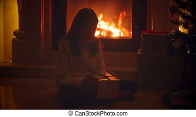 Cute girl sitting in dark living room at burning fireplace and opening box with Christmas present