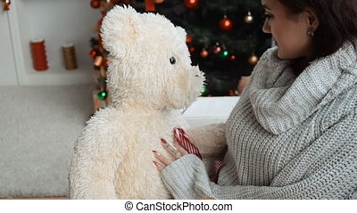 cute girl sitting near a Christmas tree and holding a big toy bear at home