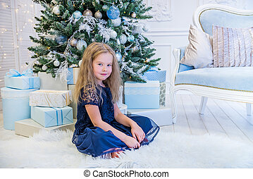 Cute girl sitting near Christmas Tree